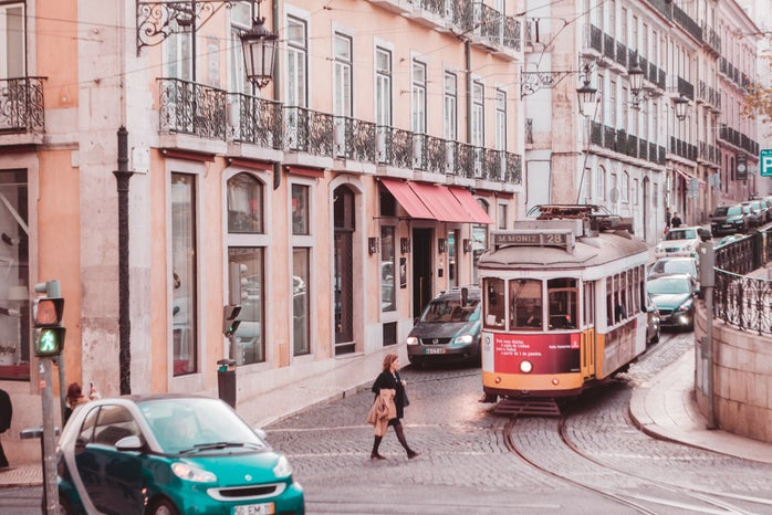 woman wearing black coat passing on road while tram is near during daytime in Lisbon, Portugal