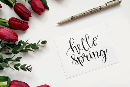 """Hello Spring"" sign with pen and roses"