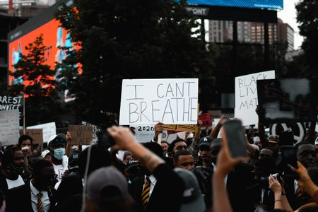 """group of protesters with someone holding a sign that says """"I can't breathe"""""""