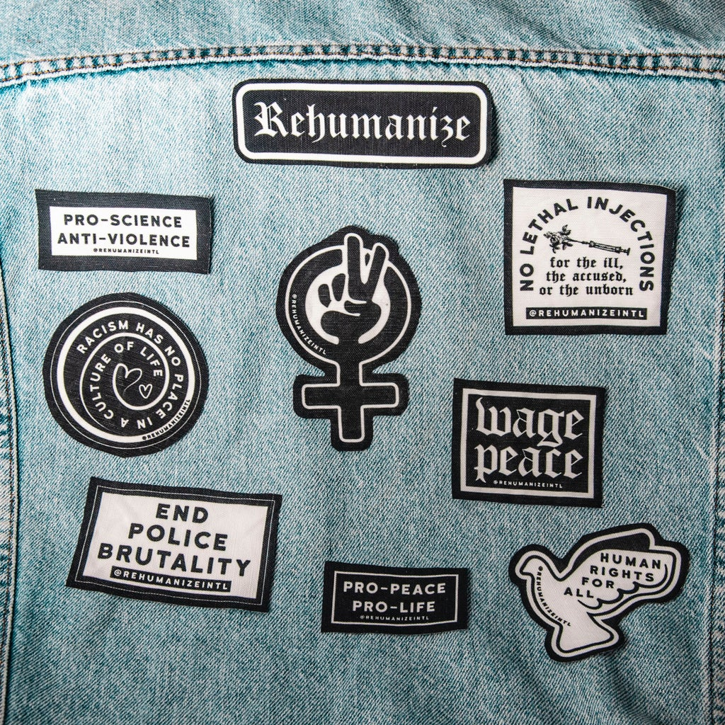 Patches on the back of an activist\'s jacket.