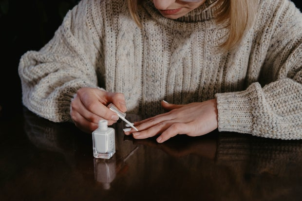 Woman in cream sweater painting her nails white on a table