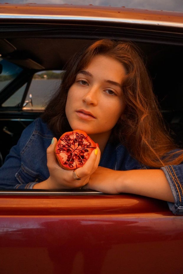 girl in car with pomegranate
