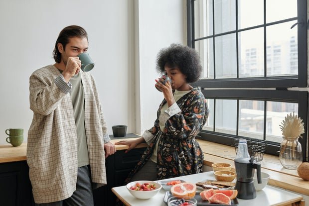 A couple standing in a brightly lit apartment drinking coffee. There is a table of fruit in front of them and they are in front of a window.