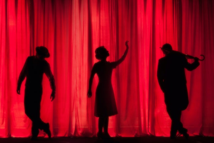 three figures in front of a red curtain