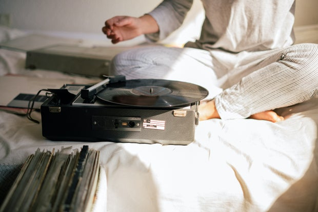 black record player on white bed sheets