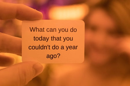 """person holding a card that says """"what can you do today you couldn't do a year ago?"""