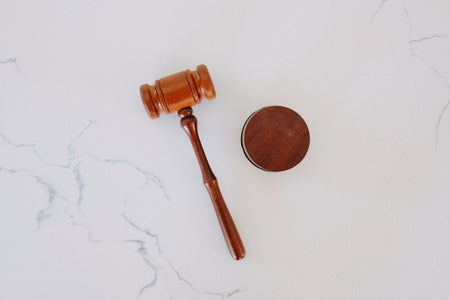 Wooden gavel on a white marble backdrop