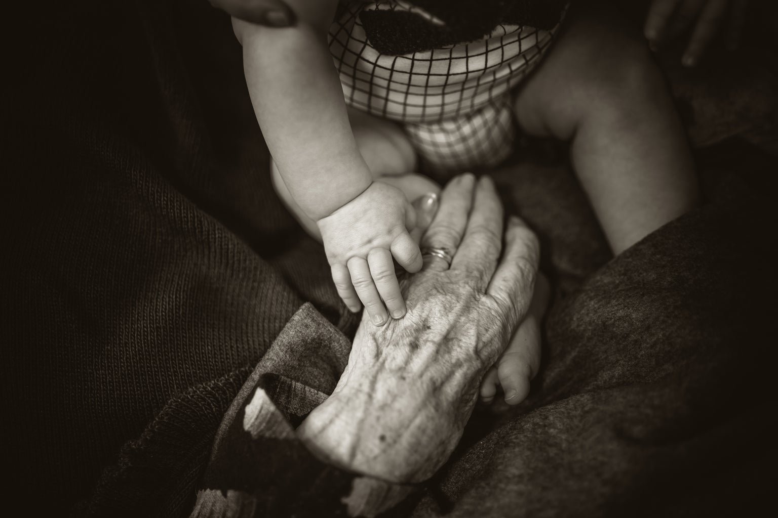 A baby holding their grandparent\'s hand.