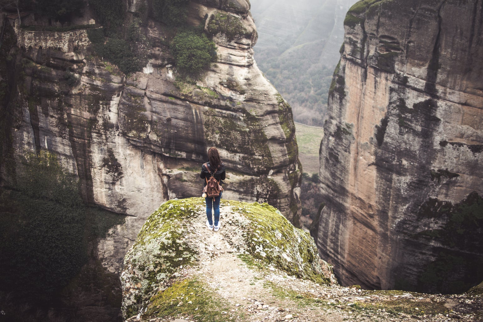 A woman with a red/brownish backpack is standing on a pathway on a cliff. She is facing the sides of two mountains.
