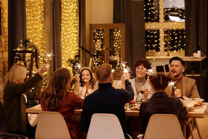A family sits around a festive dinner table with sparklers.