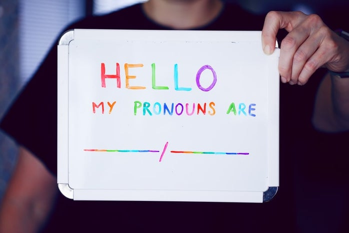 """person holding a whiteboard written \""""hello my pronouns are\"""" in colored letters"""