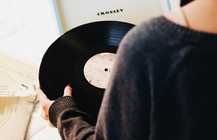 person holding a black vinyl record