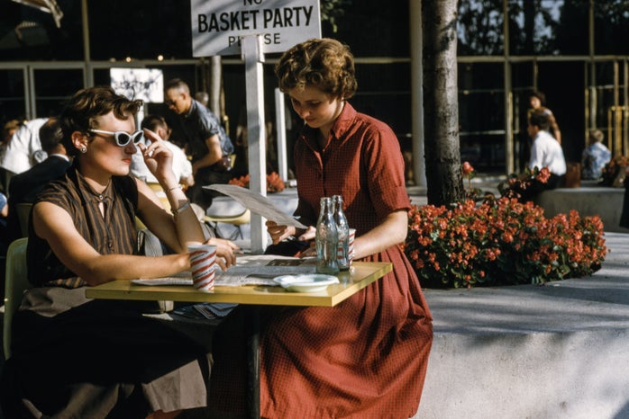 two women sitting at table outside with glasses and a newspaper