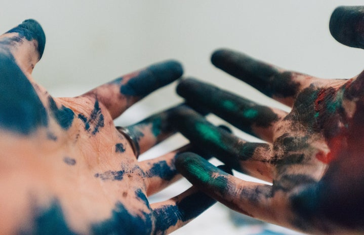 two hands covered in paint