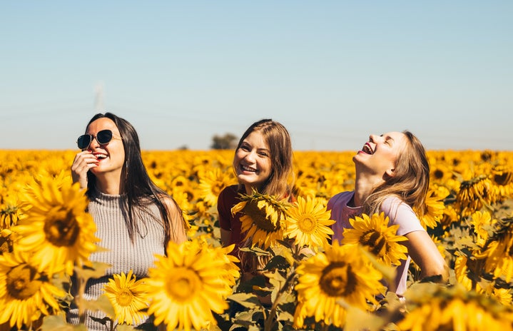 friends laughing in sunflower field