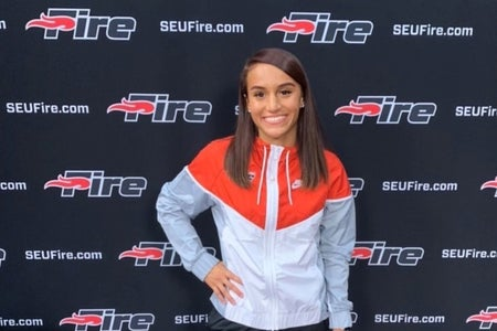 girl with red and white track jacket, posing and smiling.