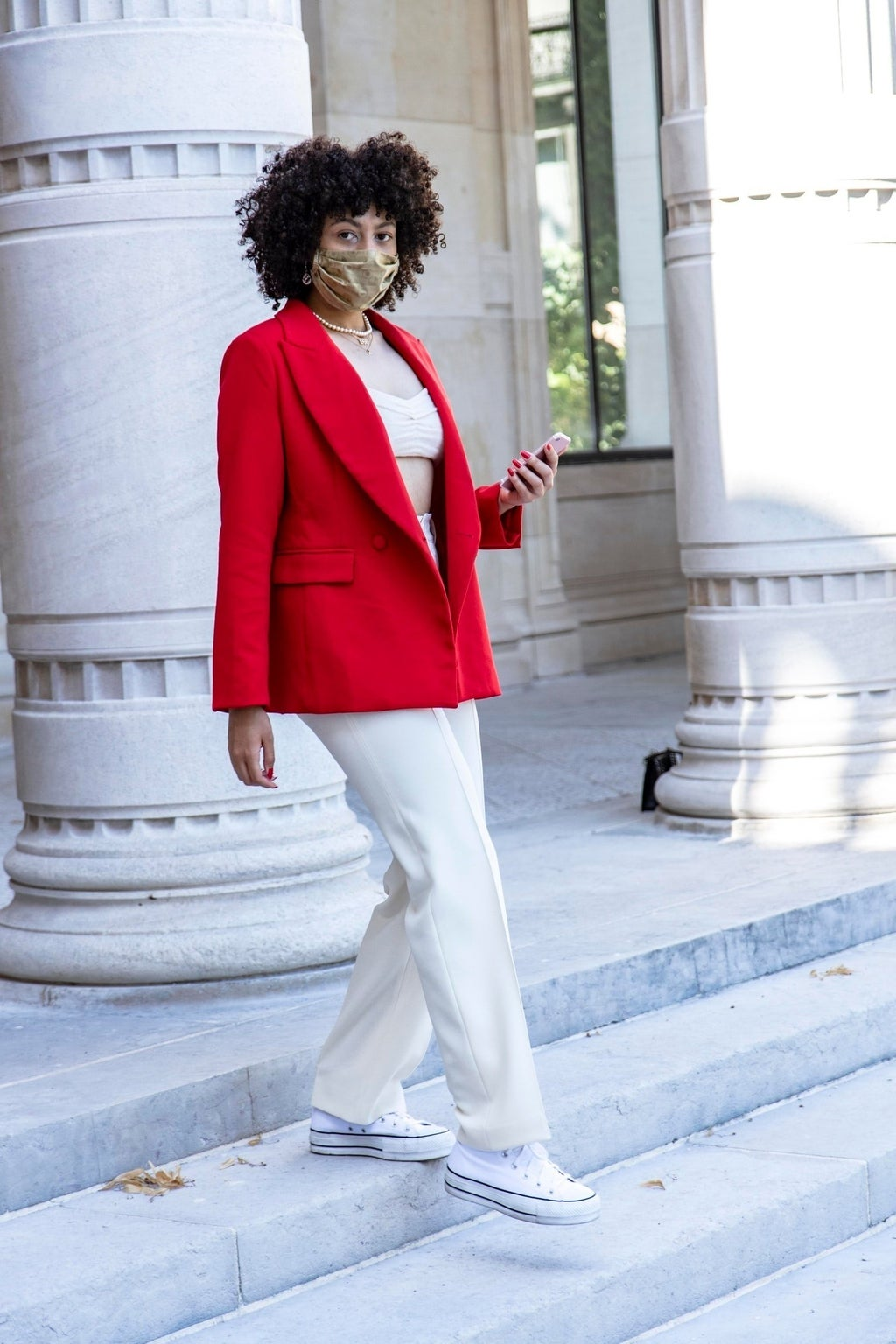 woman in red blazer and white pants with face mask walking down staircase