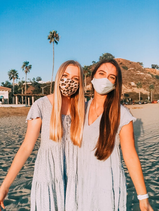 Two friends taking a walk on the beach with masks