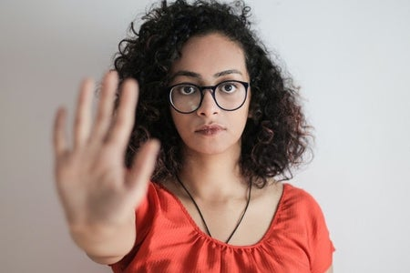 portrait photo of woman in red top wearing black framed eyeglasses holding out her hand stop gesture