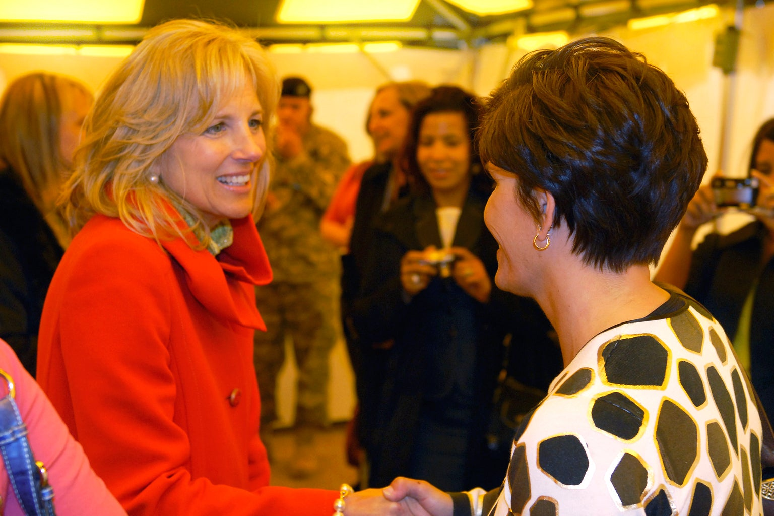 Dr. Jill Biden in a red coat, speaking to another woman.