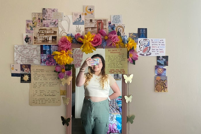 Girl taking selfie in wall mirror with art decorated around mirror.