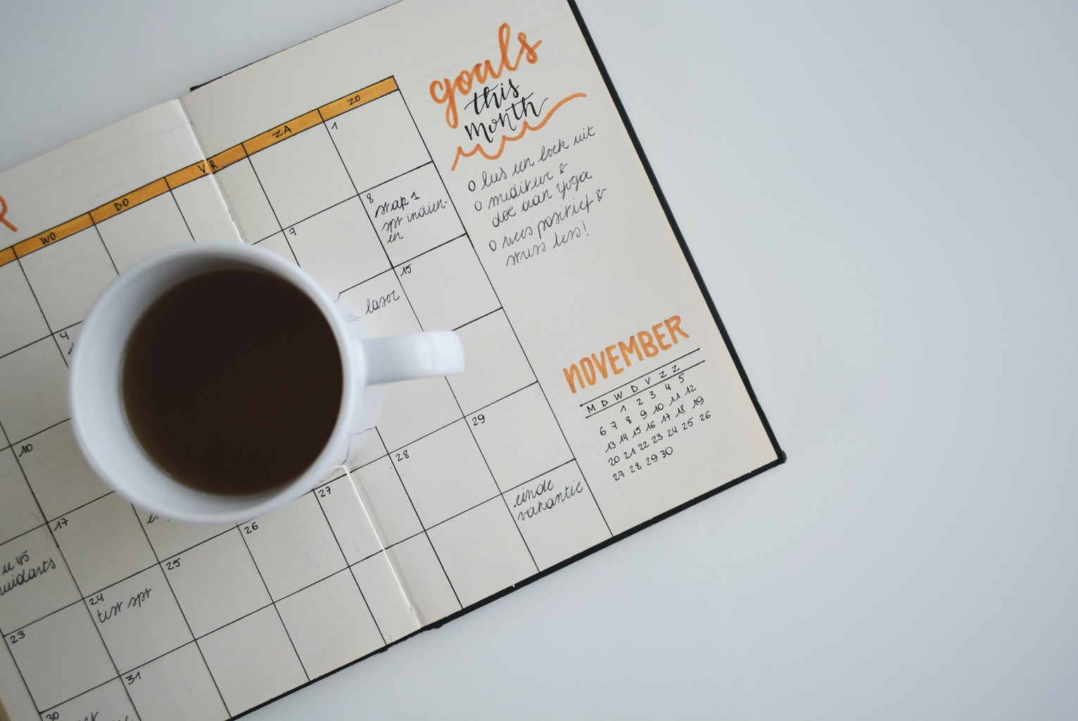 Coffee in a cup placed on top of a notebook. The notebook is lined with a calendar that has been filled out with events.