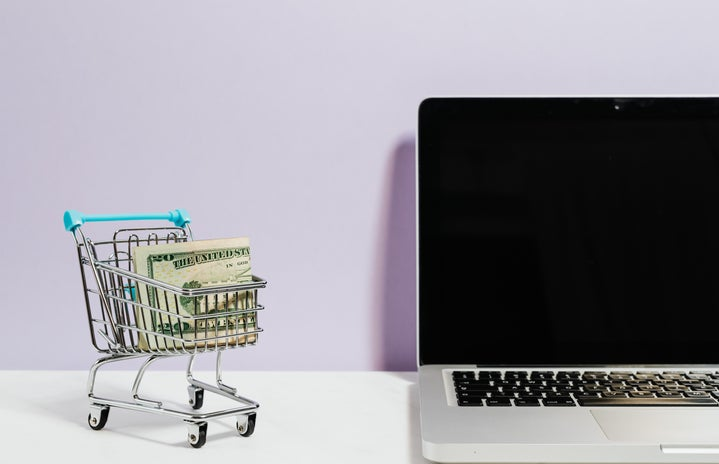 mini shopping cart with money in it next to a laptop