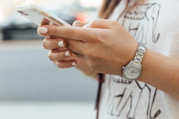 woman holding phone wearing watch