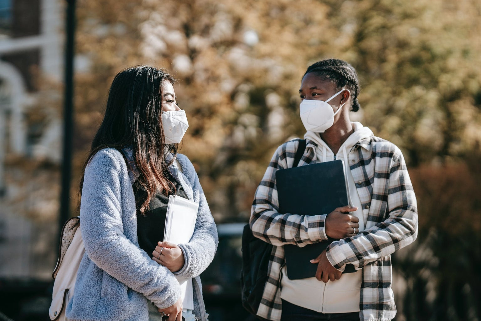 College students with masks walking across campus together.