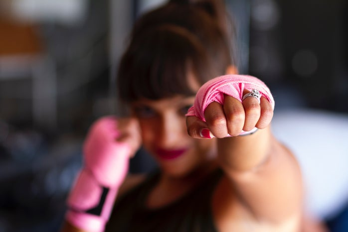 Blurred image a woman punching with pink wrist wraps on