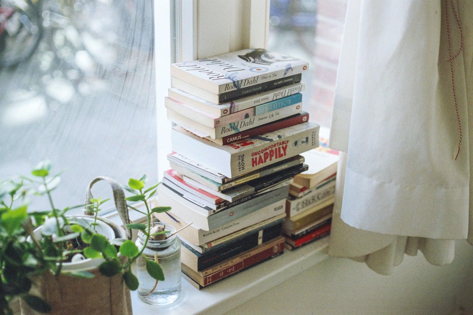 a stack of books on a window shelf