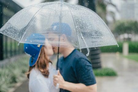 A couple kisses under an umbrella