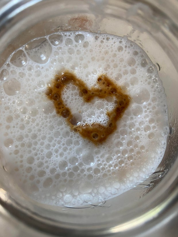 The top of a hot macchiato coffee with a heart