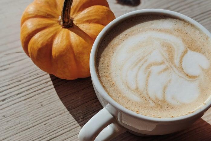 pumpkin spice latte with pumpkin next to it