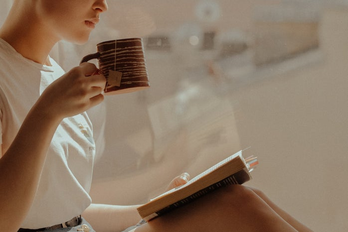 Woman reading a book by a window and drinking from a mug.