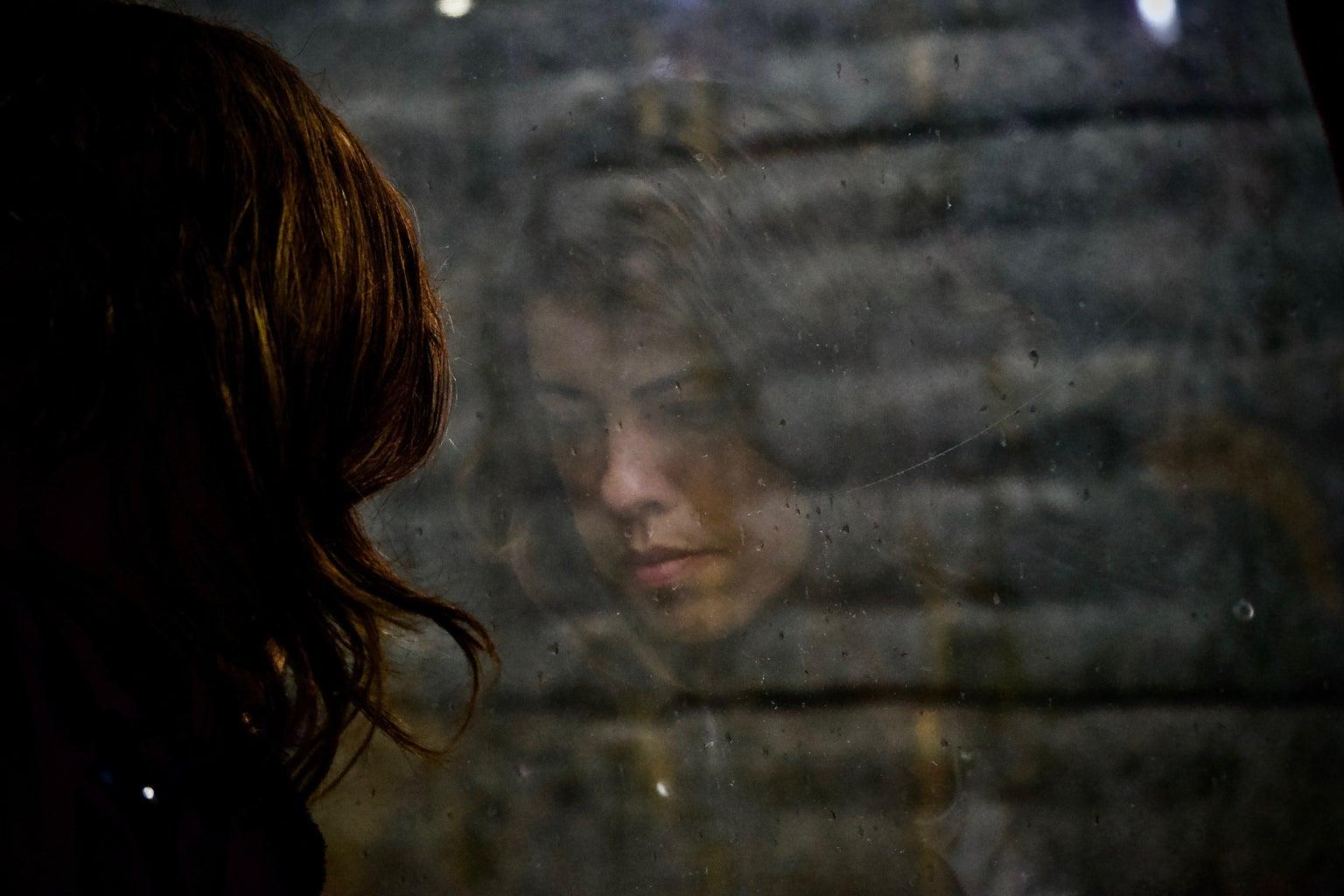 Woman staring at a window sadly