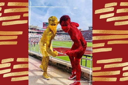 two guys covered in gold and garnet glitter posing in front of football field