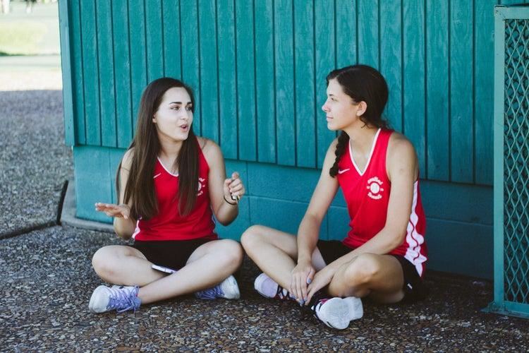 Two girls sitting on ground having conversation