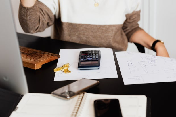 Woman using calculator while counting bills in workspace