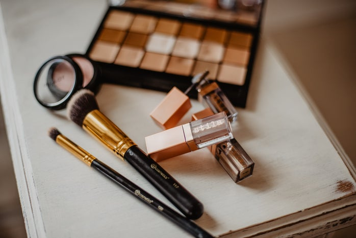 Cosmetics and brushes rest on a table