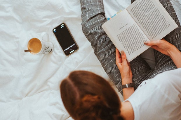 Woman sits in bed with her phone, a book and a mug.