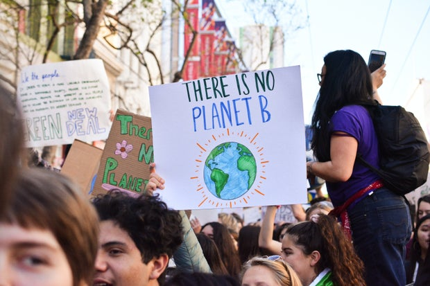 A bunch of young people holding up signs about climate change.