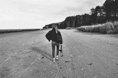 black and white photo of woman walking away on a beach