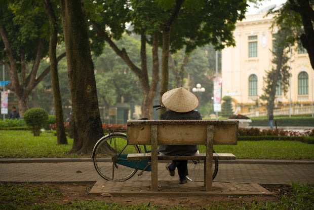 person wearing a hat sitting on bench with bike