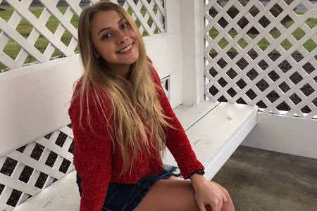 Young white woman, Tara Teipel, wearing a red top and sitting on a white bench.