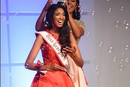Girl is being crowned as Miss Georgia Teen on a red gown