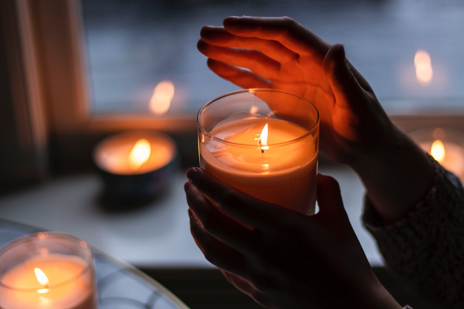 A woman\'s hand holding a burning candle