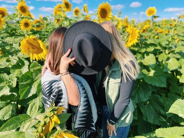 two girls smiling in a sunflower field sheaffer