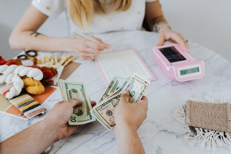 Hands counting dollar bills with woman using calculator in background