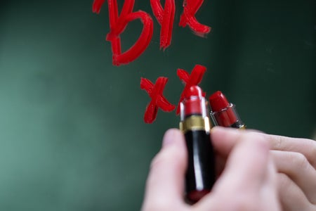 "Woman writing the word ""Bye"" on a mirror with red lipstick"